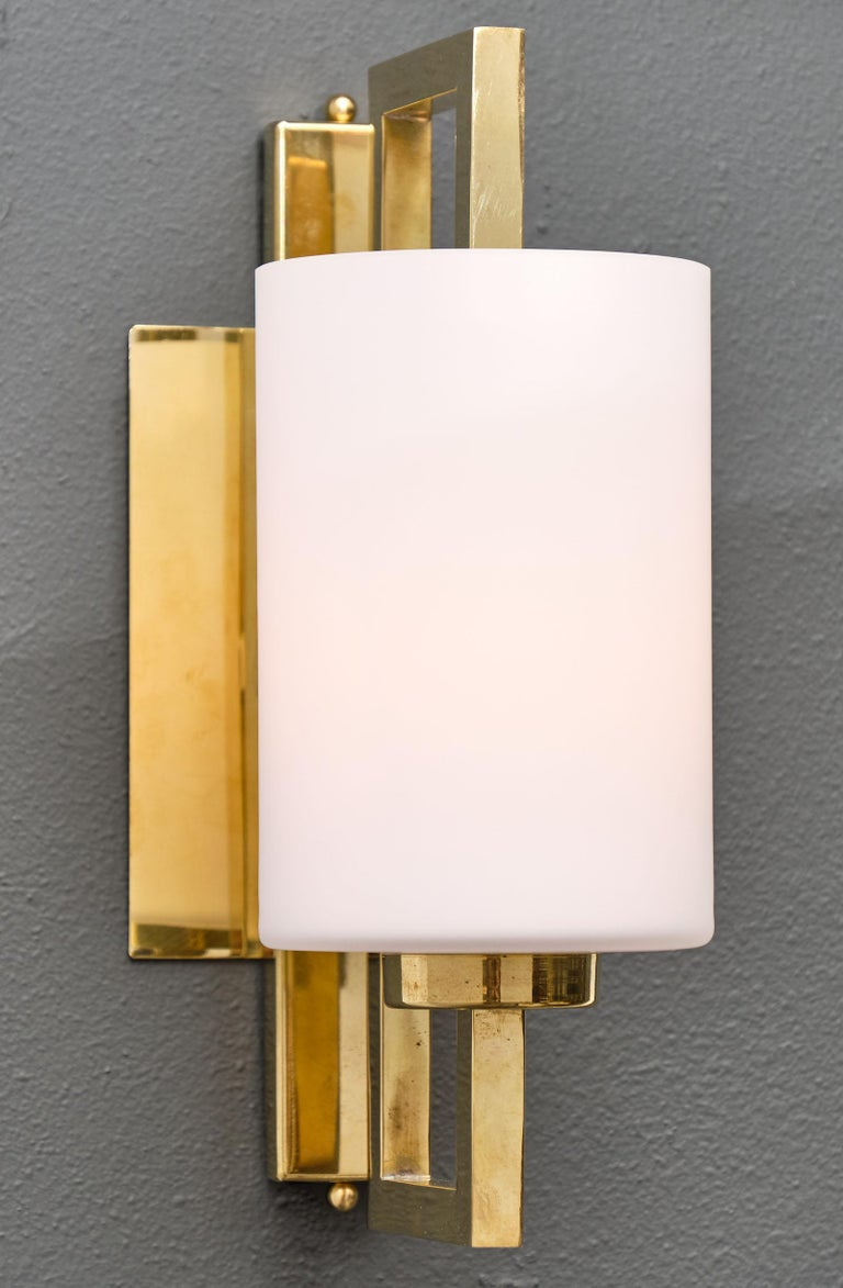 A pair of Murano glass cylindrical sconces featuring a large hand blown frosted cylindrical glass element held in its center by an opened rectangular brass structure. This pair has been newly rewired to US standard.