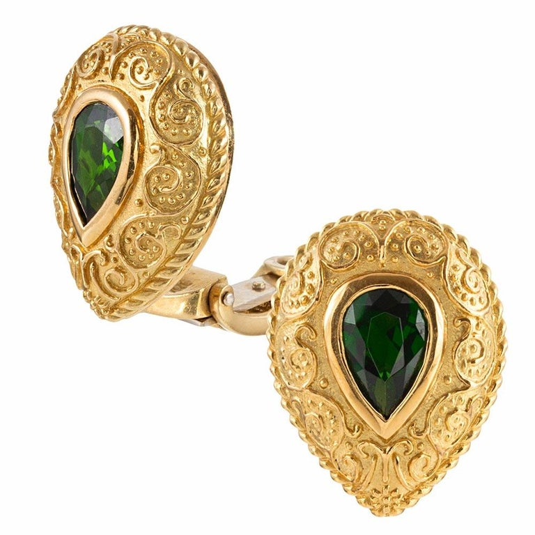 Made of 18 karat yellow gold and decorated with a modernized granulation reminiscent of Etruscan Revival, these teardrop shaped ear clips are each set with a pear tsavorite garnet. Green garnets are uncommon and even more so difficult to find in
