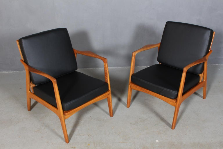 Czech design two lounge chairs new upholstered with black semi aniline leather.   Frame of oak.