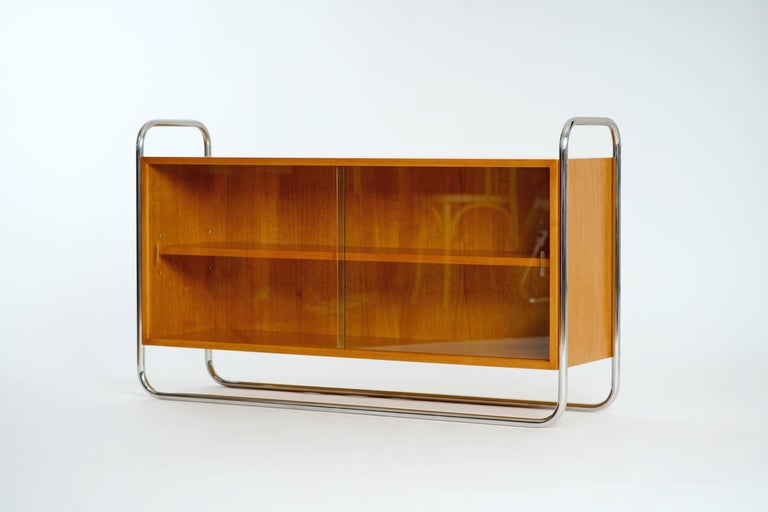 This light oak sideboard with glass sliding doors in a tubular steel frame was manufactured by UP Závody in the 1950s.  Completely restored.