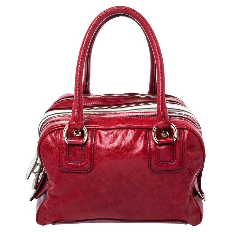 This Lily duffle bag from D & G is bound to impress and will make you stand out. Crafted from red leather, it is the perfect combination of style and functionality. It flaunts multiple zip compartments that lead to a spacious fabric interior, dual