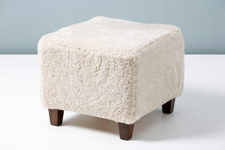 A custom made sheepskin ottoman on hardwood base with stained beech legs. The foam body is covered in premium, tufted Australian shearling.   This item is made to order in our London workshop, multiple pieces are available by request.