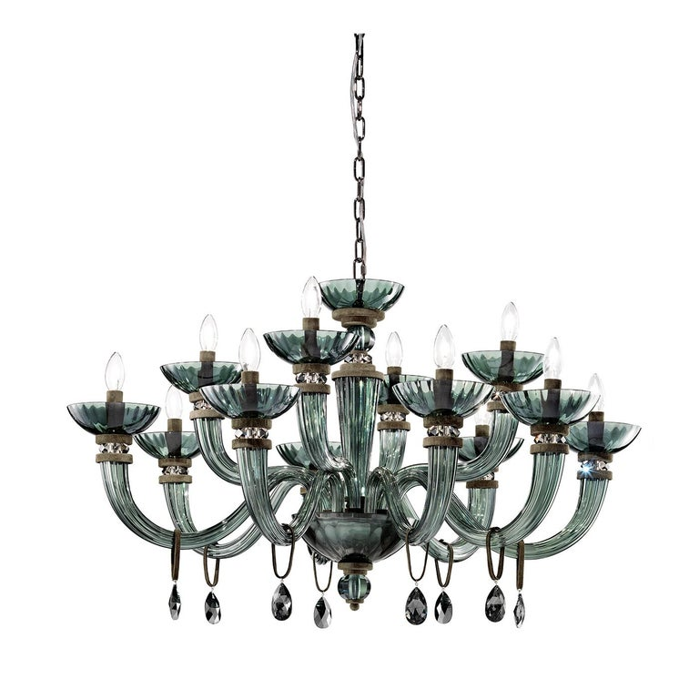 This innovative and sophisticated chandelier is handcrafted of Murano glass in a striking viridian color, and features a two-tiered structure with 8 + 4 rounded arms, glass bobeche, and a cup-shaped base with a ribbed pattern. Exquisite viridian