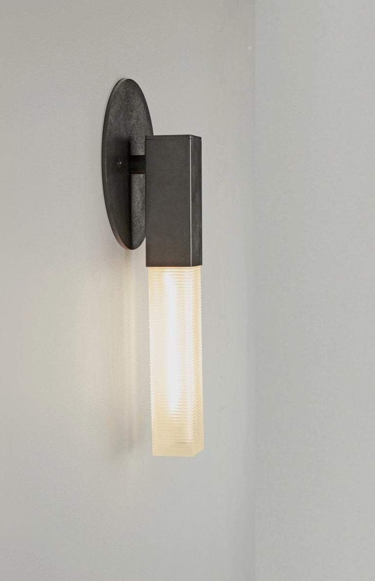 Post mini sconce Daikon  Post the mini sconce designed by Daikon's award-winning sculptor, Jury Smith, celebrates the poetic dialogue between light and form to create a modern brass fixture that leans into the timeless and iconic. Can be mounted up