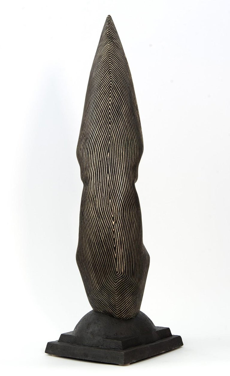 Ottawa born sculptor Dale Dunning has explored the image of the 'human head'—a universal, gender-less face for most of his career. In this beautifully cast bronze piece, a narrowed face, its forehead coming to an arrow-like point, is reminiscent of