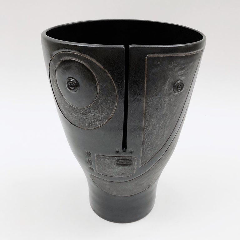 Figurative vase, called Idole, ceramic enameled in black and cloudy dark grey, decorated with a stylized visage and abstract designs incised front.  One of a kind and exclusive handmade piece, designed and signed by the French artists and