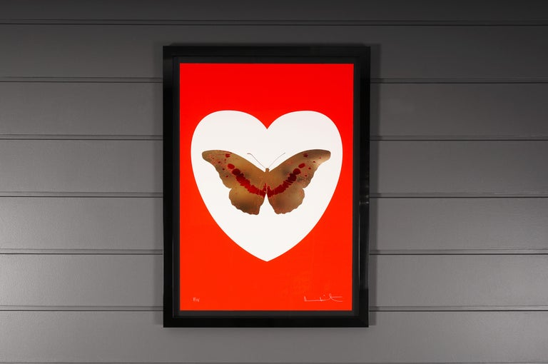 The 'I Love You' Butterfly in a bright poppy red and gold color scheme is a limited edition silkscreen print by Damien Hirst. This particular work features a gold and red foil block butterfly, surrounded by a white heart and set on the vivid