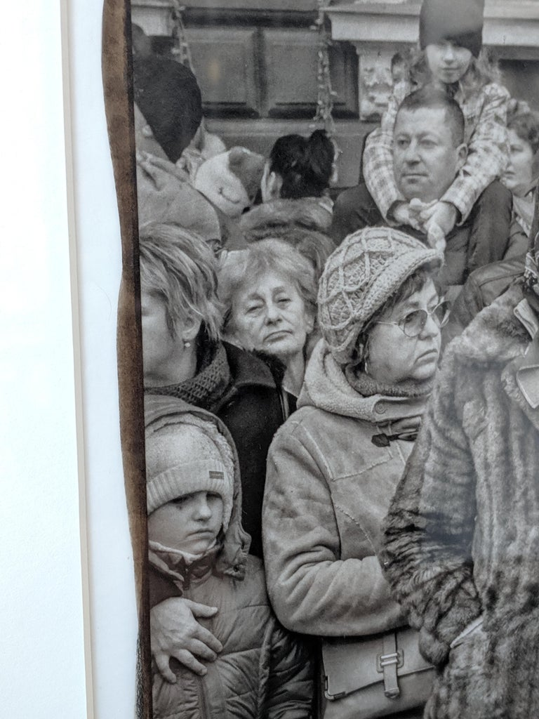 This fine art photograph shows parade watchers in Romania. The most compelling face in the crowd stands at the center; it is an older woman with a faded fur coat. The rest of the crowd, of various ages, frames the central figure, each lost in their