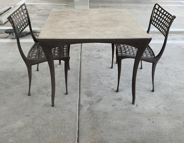 A Dan Johnson designed set for Brown Jordan. The original glass has been replaced with a beautiful piece of travertine. The chairs measure approximately 20 inches wide, 21 inches deep, 23 inches tall and 17.5 inches seat height. The table is 35.5