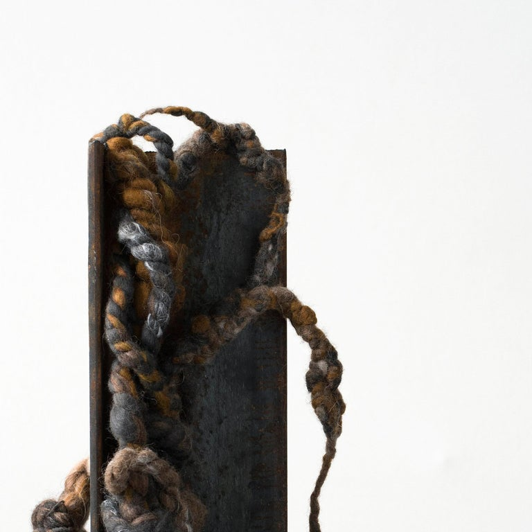 The piece combines a Picasso marble chunk and a weathered steel angle with exotic fibers knotted, twisted and entangled into a small 'Cling' sculpture. The base is blackened steel.