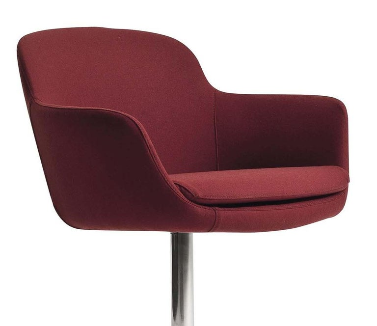 Modern and elegant, this swivel armchair will add movement to any space with its Mid-Century Modern design and cushioned shape that conforms to the body. The cozy barrel-shaped seat is upholstered in red fabric (col. 1520/72 cat. Extralux) and sits