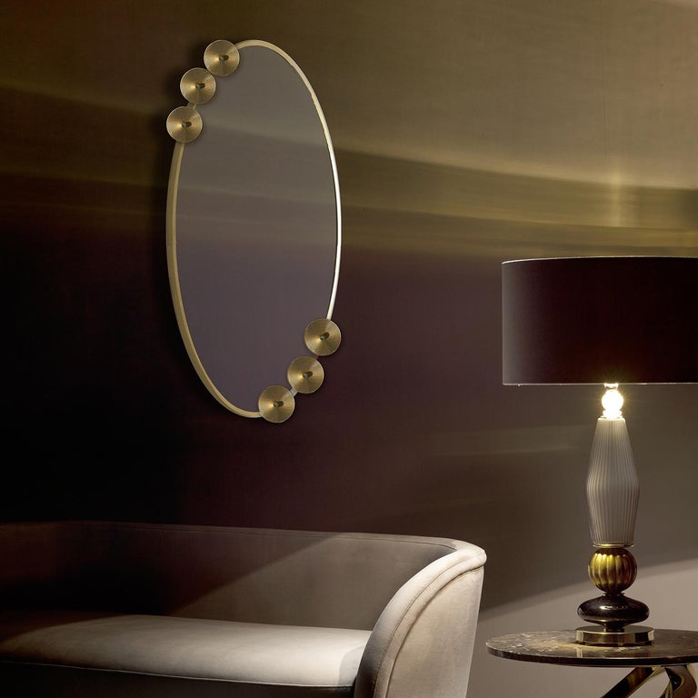 A superb example of artistic craftsmanship, this exquisite mirror is an eye-catching decoration for the wall. Its oval glass frame with an antique gold finish is adorned with two sets of three disks that add a unique embellishment to this piece and