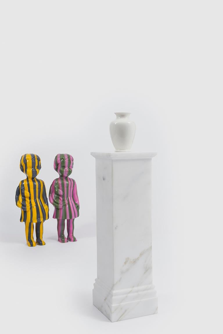 Pedestal Vase is a series of miniature vases. The archetypal porcelain vase is placed on a pedestal that has the double function of also containing the cylinder that holds the water. The exaggerated relationship between the base, available in either