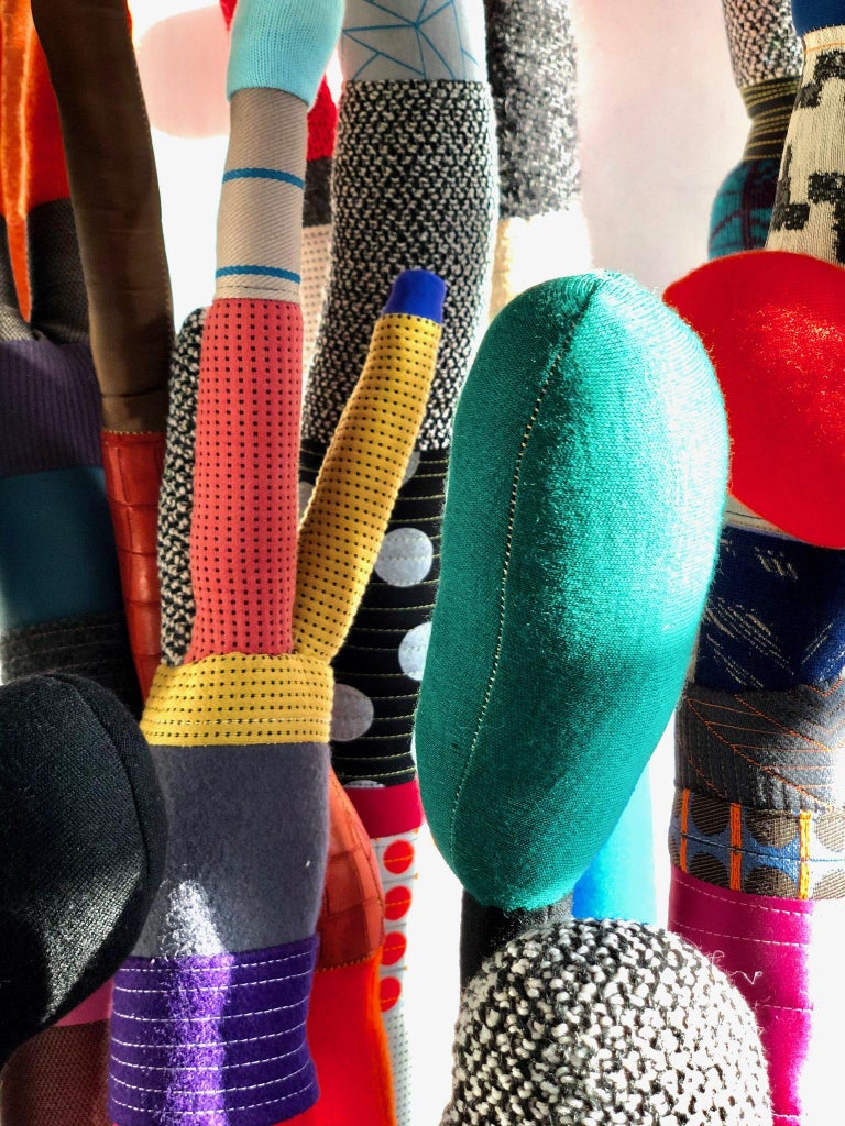 """Growing out of scraps forest - These banded multicolored sculptures are created through repurposing fabrics scraps that are molded into unique figures to create a forest of """"nonsense."""" Each one is named for a friend, family member, lover, pet, or"""