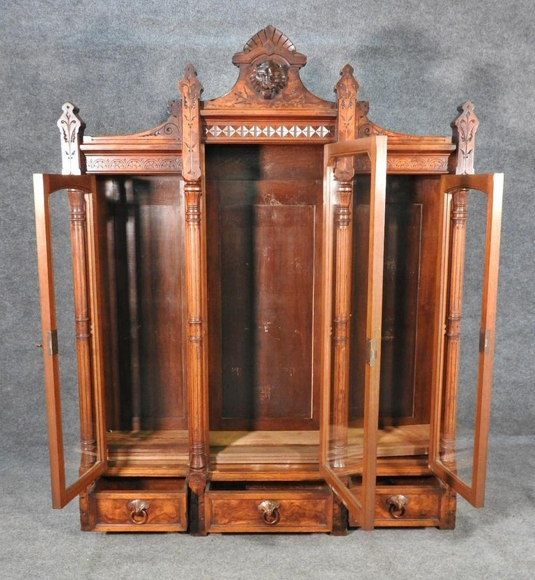 This is a rare Daniel Pabst carved walnut bookcase in the Renaissance Revival style. The bookcase is of fantastic form and in good original condition. It features 3 glass doors containing 3 shelves. 3 dovetailed drawers. Figural. Measures: 74