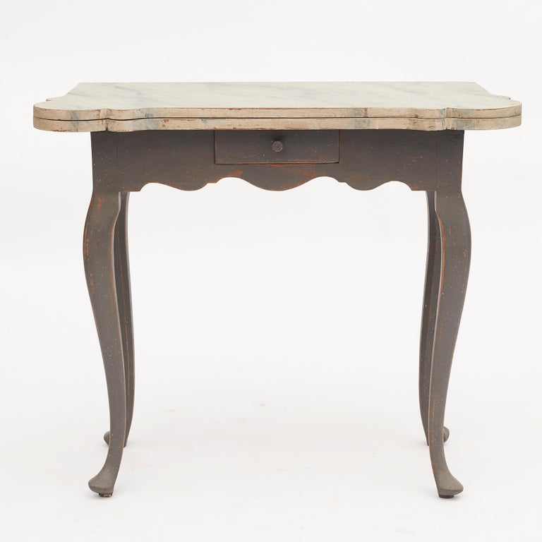 Danish 18th century rococo console and gaming table. The top lifts to reveal an interior with candle stands and guinea cups. Table of rectangular form when it is closed with four cabriolet legs and 1 drawer. Table top light grey marbled, legs