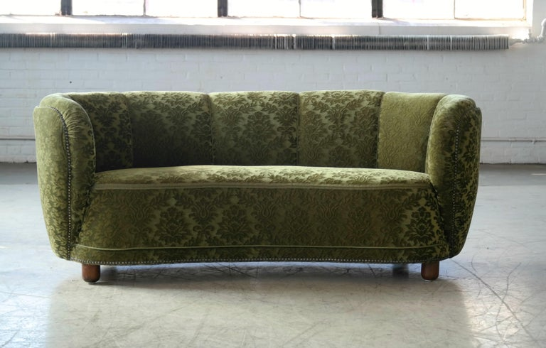 Beautiful and very elegant 1940s curved three-seat sofa in green velvet fabric. The sofa has springs in the seat and the backrest and the cushions are nice and firm and the sofa very sturdy. The sofa has been re-upholstered in the past and the