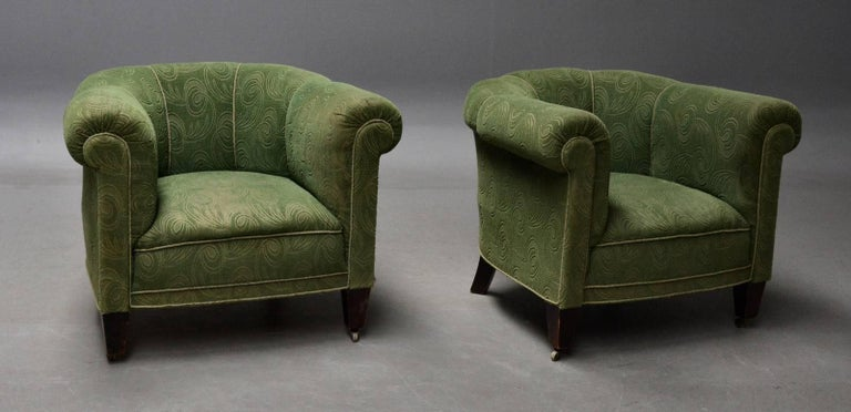 Danish 1950s Chesterfield style pair of club chairs very similar to some of famed Otto Schulz' designs from the 1940s. Sturdy and solid raised on legs of stained beech with wheels on the front legs. Fabric is clean but shows signs of moderate wear