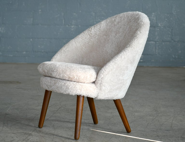 Classic easy chair with curved back and legs in solid oak designed by Ejvind A. Johansson in 1958 as Model 301 for Gotfred H. Petersen. Newly refurbished and re-upholstered in putty colored curly fancy shearling sheepskin from Dualoy. Super