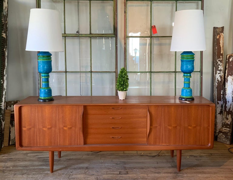 A beautiful and handsome 1950s Danish teak credenza cabinet, with sliding doors with integrated sculptural handles, which conceal adjustable shelves in the left and right side, and a bank of graduated drawers in the center. Raised on teak legs, this