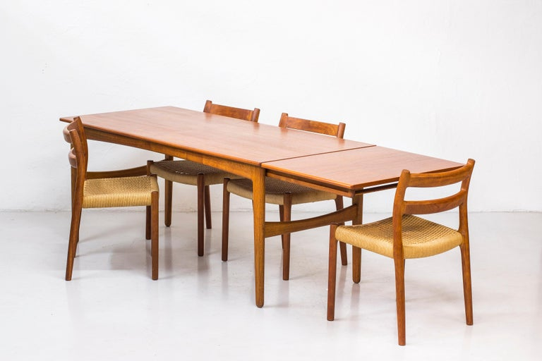 Dining table design by Knud Andersen in Denmark during the 1950s. Produced by cabinet maker J. C. A Andersen. Solid oak legs with teak tabletop. Tabletop extensions on each side hidden underneath the main table. Sits eight to ten people with ease.