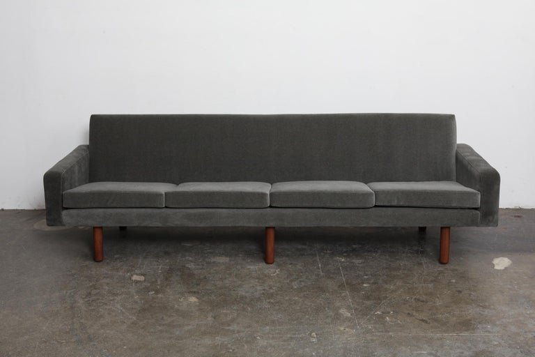 Danish 4-seat 1960s fabric sofa with 4 loose seat cushions and tight back style and straight clean lines throughout, sitting on 6 tapering solid teak legs (that have been refinished). Newly upholstered in a grey mohair/velvet fabric, teak legs
