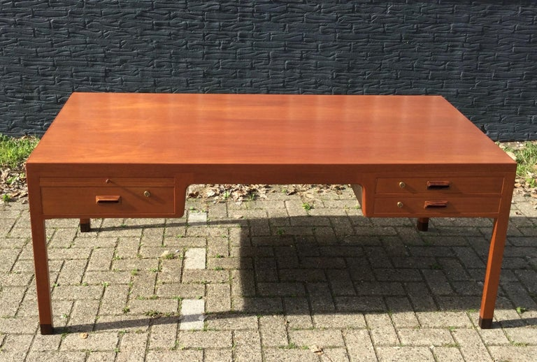 Exceptional high quality crafted Danish desk by Aksel Bender Madsen & Ejner Larsen from the mid 1960s. The desk is executed in mahogany (looks like teak) with beautiful details, amongst: one pull out tray with glass top (last picture) to be found