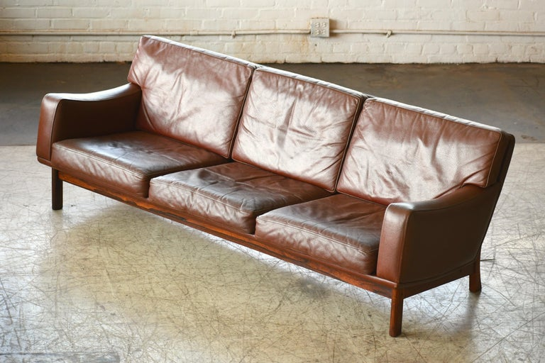 Fantastic Danish modern large-size three-seat sofa designed and manufactured by Erhardsen & Andersen (Eran) in the late 1960s. The design is low and wide and epitomize Danish design of the late 1960s. High quality buffalo hide raised on a frame and
