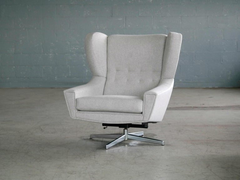 Exciting and very cool Space Age swivel chair attributed to Designer, Illum Wikkelso for Nielaus Jeki Mobler. Made in the latter part of 1960s it features a beautifully rather exuberant and very comfortable wing back design on an aluminum swivel