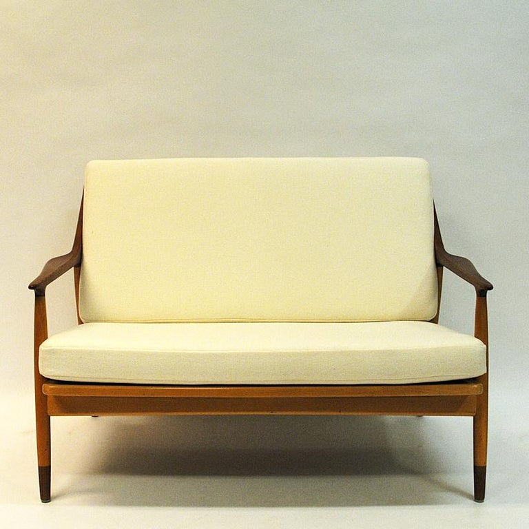 Danish Modern love seat newly upholsthered in a Norwegian cream white whool fabric named Amdal 100 from Gudbrandsdalen Uldvarefabrikk. This 2-seater sofa is designed by Kurt Østervig for Jason Møbler in Denmark 1950s, and has a solid beech wood