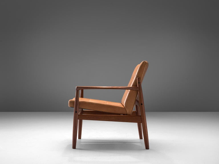Armchair, walnut and oak, Denmark, 1950s  This lounge chair in oak presents an open-arm frame. The lounge chair is upholstered in cognac fabric which shows a subtle patina. This design features elegant details such as the pointy armrests that are