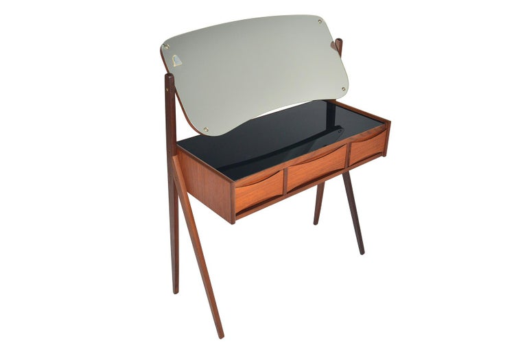 This gorgeous Danish modern Arne Vodder teak V-legged vanity offers wonderful lines in a small footprint! Featuring an articulating vanity mirror, this piece has ample storage with three drawers and a black glass, lined top. In excellent original
