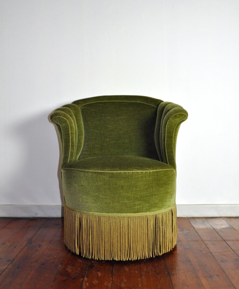 Voluptuous Art Deco chair executed with wooden legs, green velvet and fringes (can be removed). High lined and curved back and backrest.