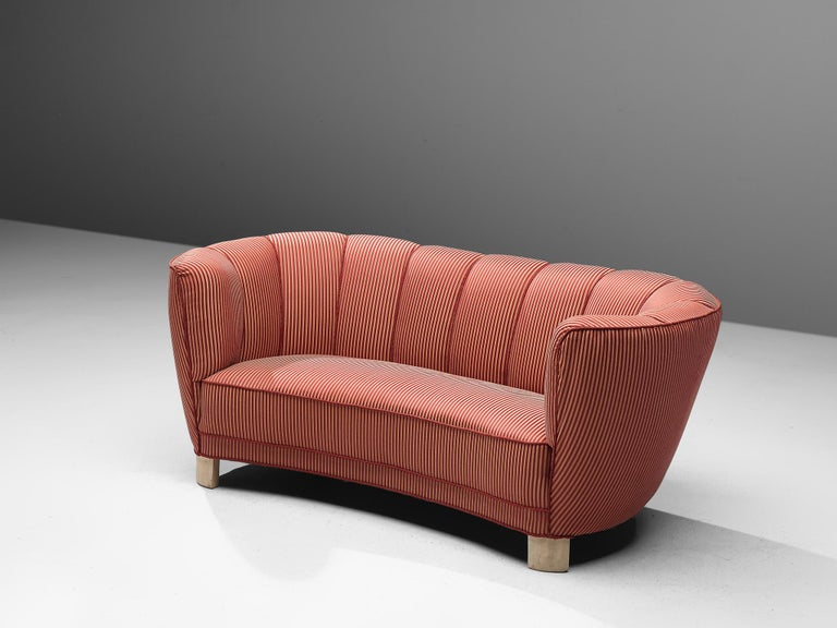 Banana sofa in red and white striped upholstery and wooden legs, Denmark, 1940s.  This voluptuous sofa is executed in a striped fabric with wooden legs. The sofa has a high lined and curved back, while the backrest is horizontal straight and flows