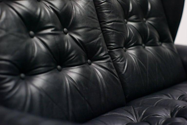 Very comfortable black leather Danish sofa on dark brown dyed maple legs. Scandinavian classic in the style of Danish masters like Finn Juhl, Arne Vodder, Hans Wegner and Arne Jacobsen.