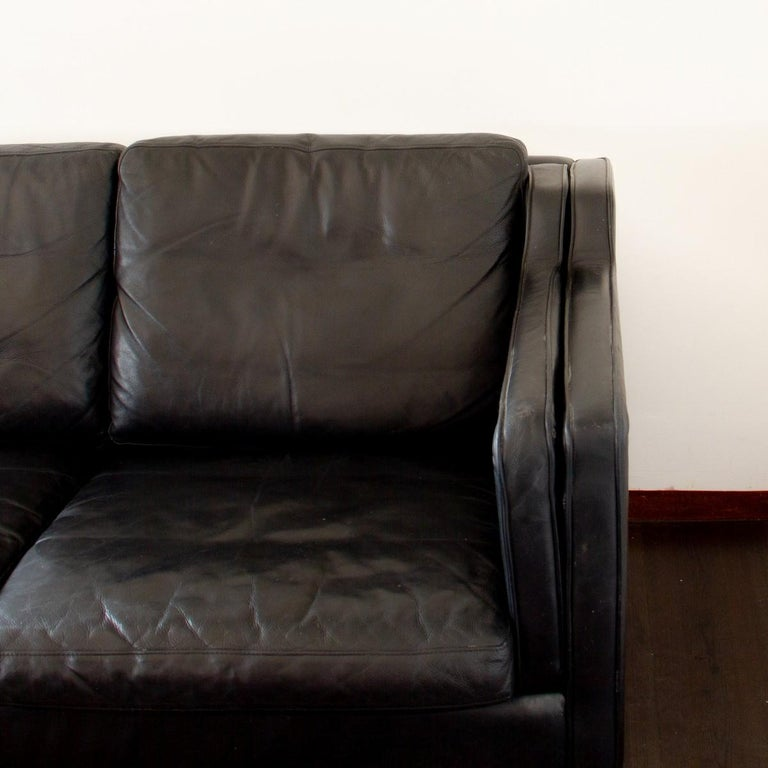 A Classic Danish modern three-seat sofa in black leather with beech feet. 
