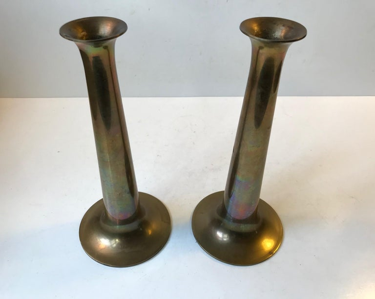 This pair of candlesticks was designed by Hans Bolling and manufactured by Torben Ørskov in Denmark during the 1960s. They are made from solid brass and feature the manufacturer's mark to each base. Please notice the beautiful rainbow patina they