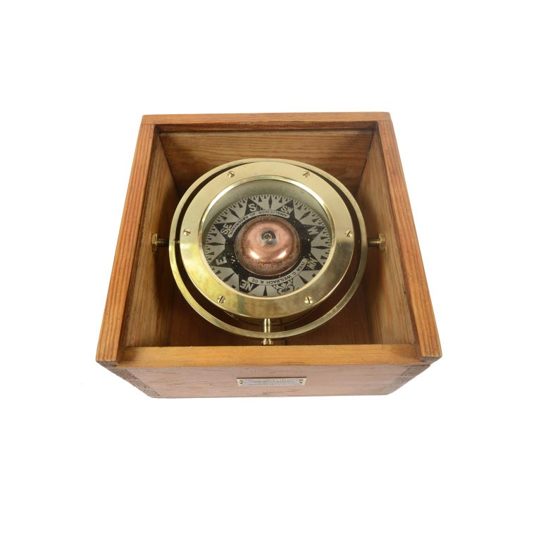 Magnetic compass on universal joint in its original wooden box with slot lid, produced by Iver C. Weilbach & Co Amaliegade 30 Copenhagen. The compass consists of a cylindrical vessel of brass and bronze, called a mortar, on the bottom of which is