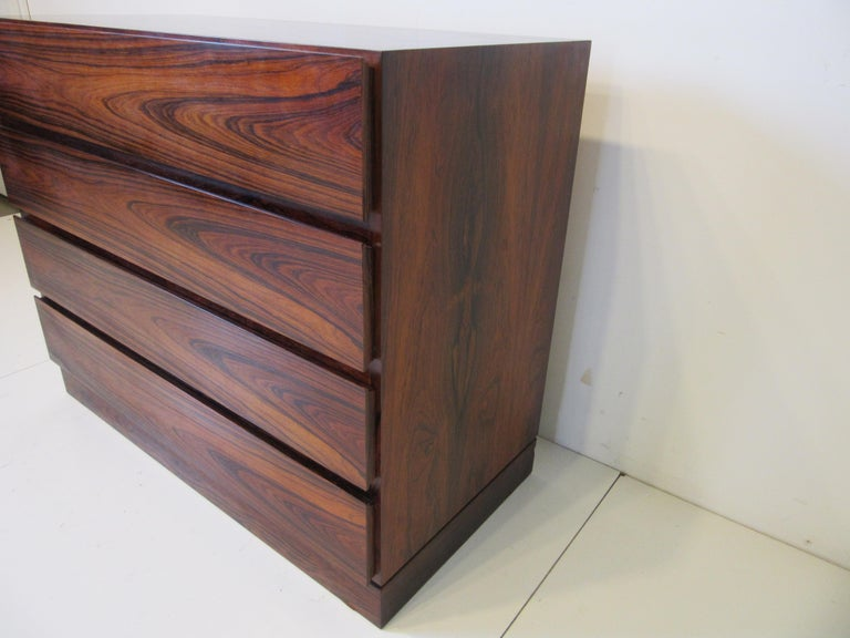 A rich well grained Brazilian rosewood four drawer dresser with the lower part of the drawer fronts curved for finger pulls . manufactured and ink stamped to the bottom of the base Made In Denmark, a great eye catching design that is well crafted.