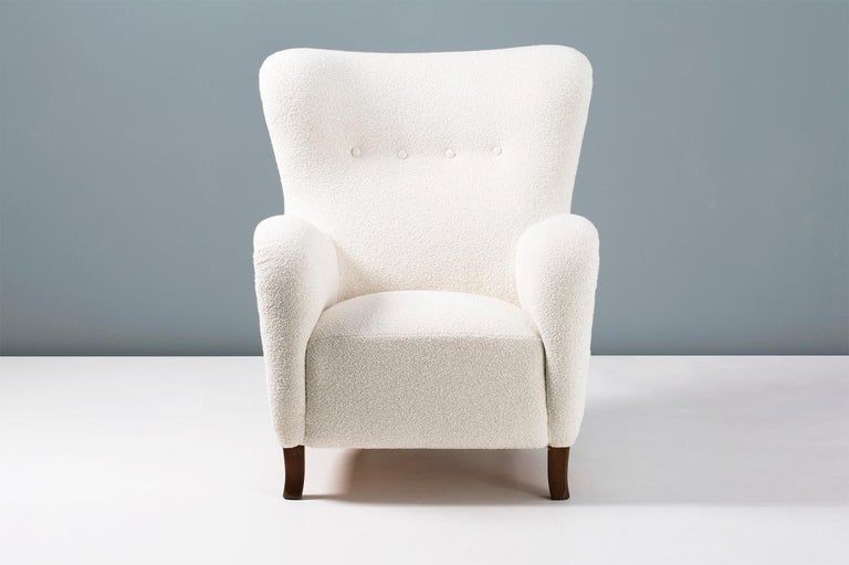 1940s vintage wing chair in the manner of Fritz Hansen, produced in Copenhagen by Christian Sorensen & Co. The legs are stained beechwood and the chair has been reupholstered in luxurious bouclé fabric composed of cotton and wool.  Pair available