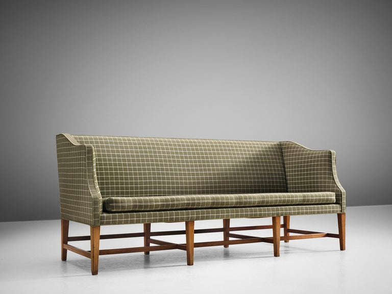 Danish cabinetmaker, fabric, mahogany, Denmark, 1950s.   This free-standing three-seat sofa with has eight profiled mahogany legs. The sofa is upholstered with a white and green checked fabric. The sofa features ornate forms and shapes and holds a