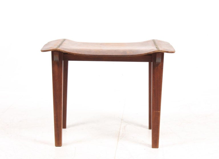 Stool in solid teak and seat in patinated leather. Made by Danish cabinetmaker in the 1940s.