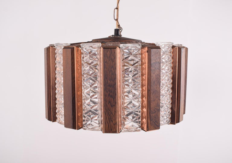 Scandinavian Modern ceiling lamp in brass, glass and teak. Round with alternating yellow and amber colored glass bricks and wooden slats mounted on brass plates. Lamp is suspended in a brass chain, which can be shortened is desired. Emits a warm and