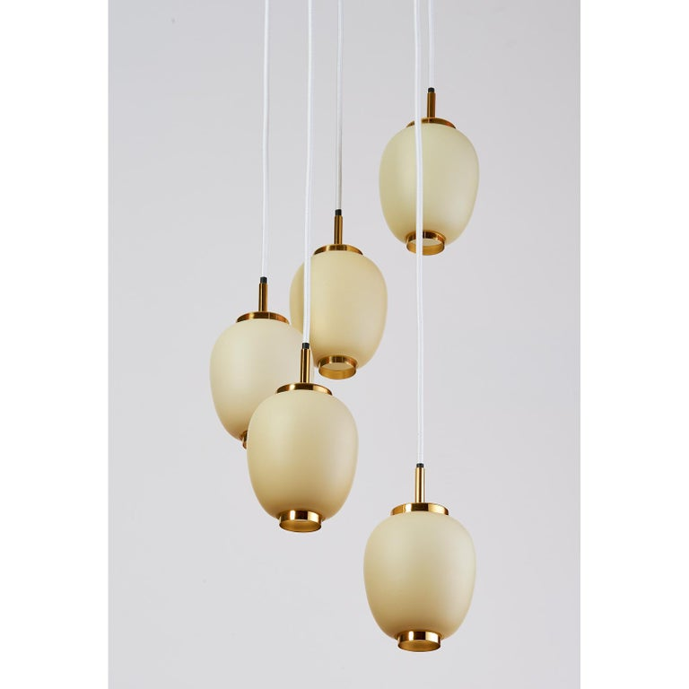 Denmark, 1960s. Pendant chandelier with five adjustable oval glass opaline shades mounted on polished brass mounts Suspended on white fabric cord Dimensions: 50 height x 12 diameter Rewired for use in the USA.