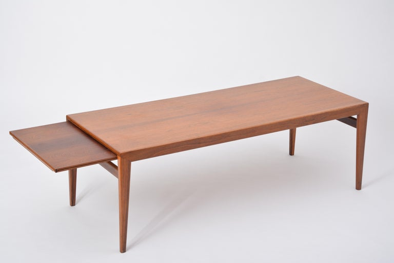 Extendable Danish Mid-Century Modern coffee table by Johannes Andersen  This coffee table is made of wood and features two extensions. One of the extension features a formica top. It was designed by Johannes Andersen in the 1960s and produced by