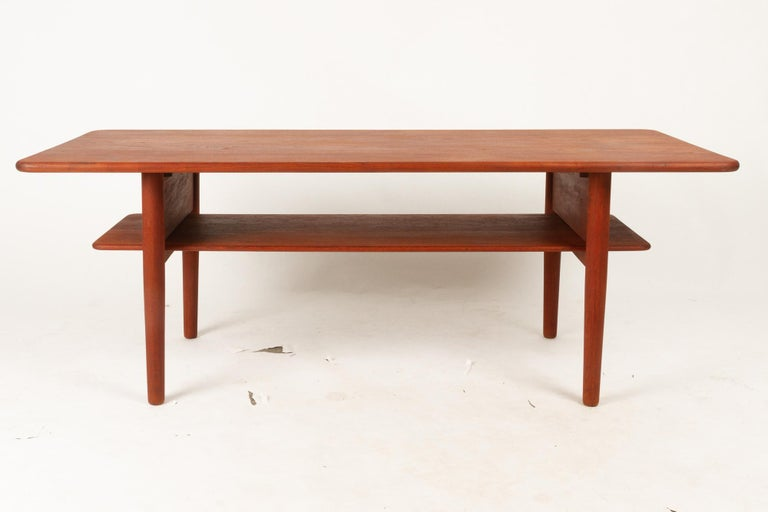 Danish coffee table in solid teak with underlying shelf. Rare model by Danish architect Ib Kofod-Larsen in solid teak. Designed in 1952, made by Christensen & Larsen. Good original vintage condition. Beautiful patina. Gently cleaned and oiled.