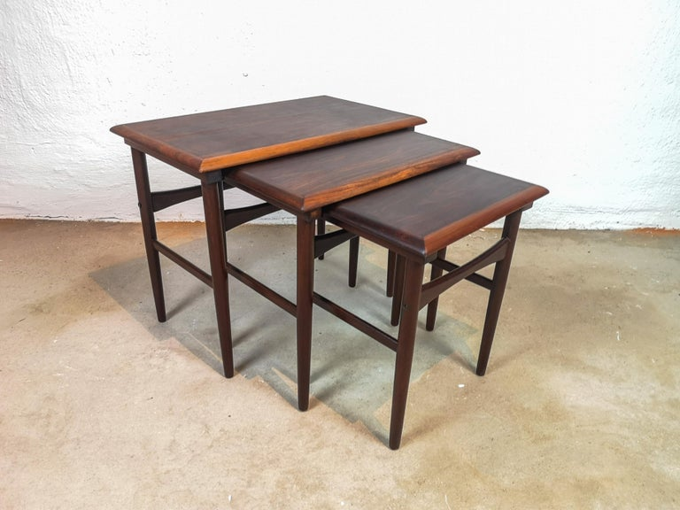 This set of three rosewood tables attributed to Kai Kristiansen and produced by Skovmand & Andersen, circa 1960-1969. The tables are made of legs with solid rosewood and the top with rosewood veneer. The two smaller tables slide under the main table