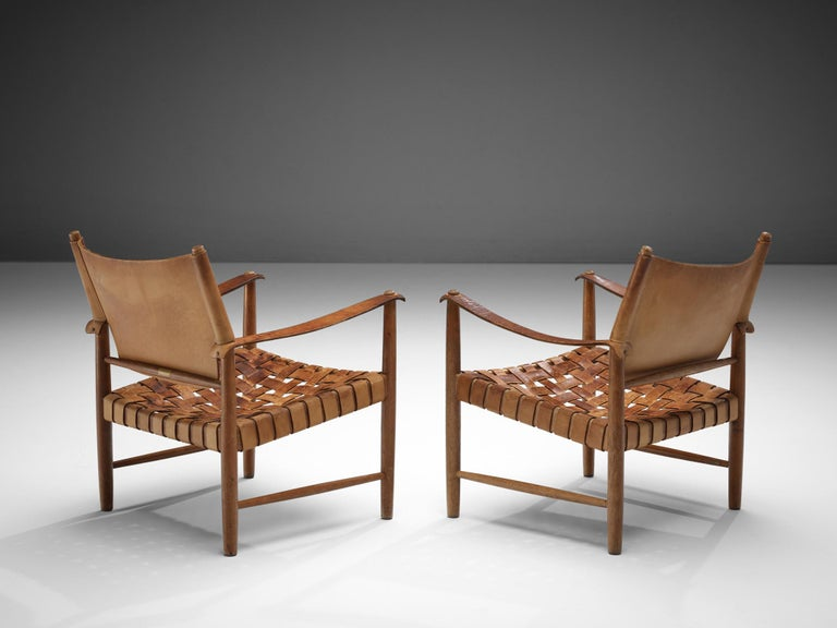 Pair of Danish safari chairs, patinated leather, oak, Denmark, 1950s.  This elegant set safari chairs features wonderful patinated leather on both the seat, the arms and back. The patina creates a vibrant look which you can only achieve after years