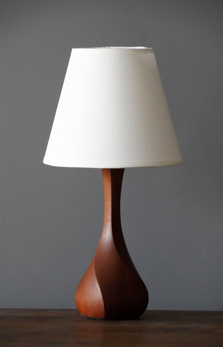 A finely sculpted teak table lamp. Produced in Denmark, 1960s. 