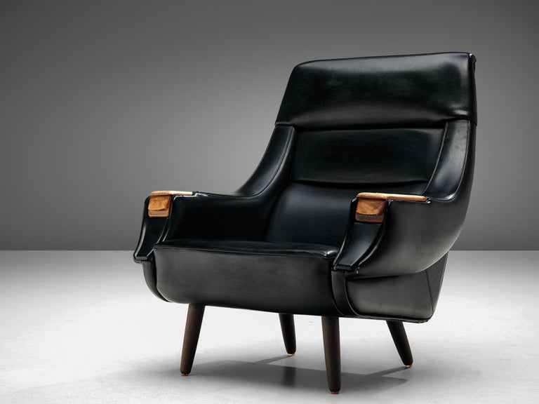 Henry Walter Klein for Bramin, lounge chair, black leatherette, wood, Denmark, 1960s.  Robust and comfortable lounge chair by the Danish designer H.W. Klein. The slightly curved shape of the backrest has a highly inviting appearance. The chair has